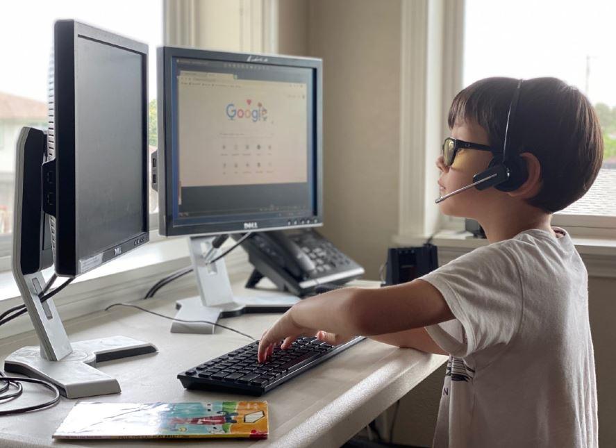 Child wearing headset at desktop computer remote work