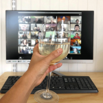 Holding a glass of white wine up during a virtual chat for virtual happy hour
